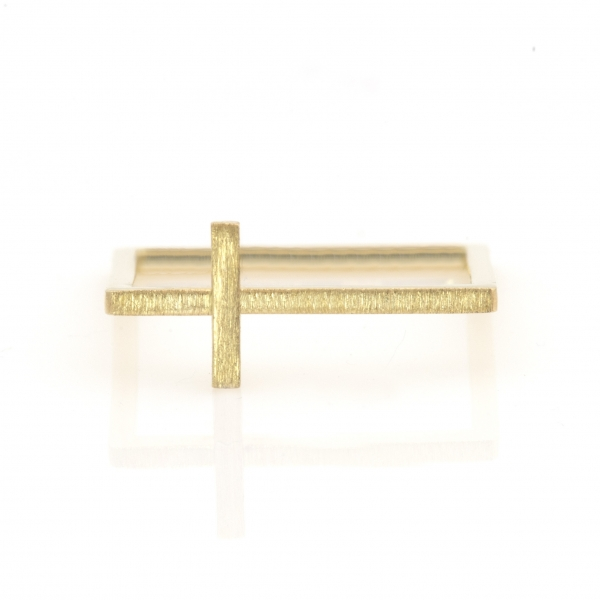 Złoty krzyżyk na kwadratowym pierścionku.