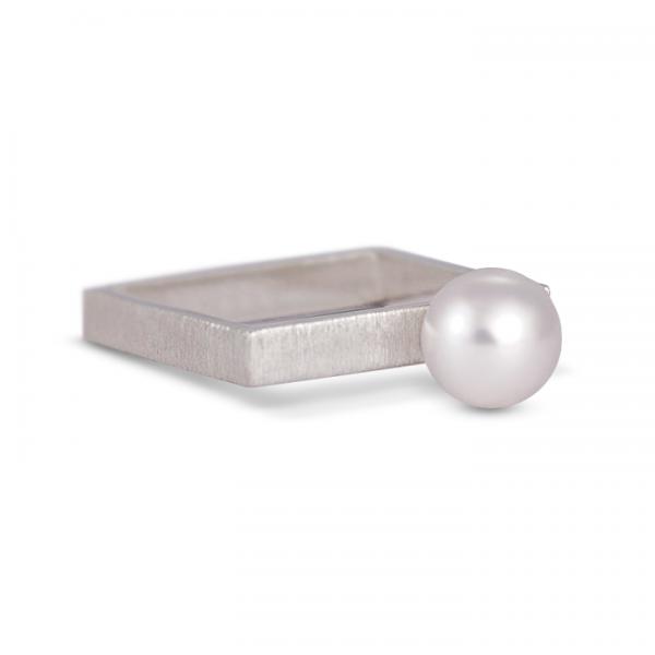 Srebrny pierścionek-kwadrat z białą perłą.