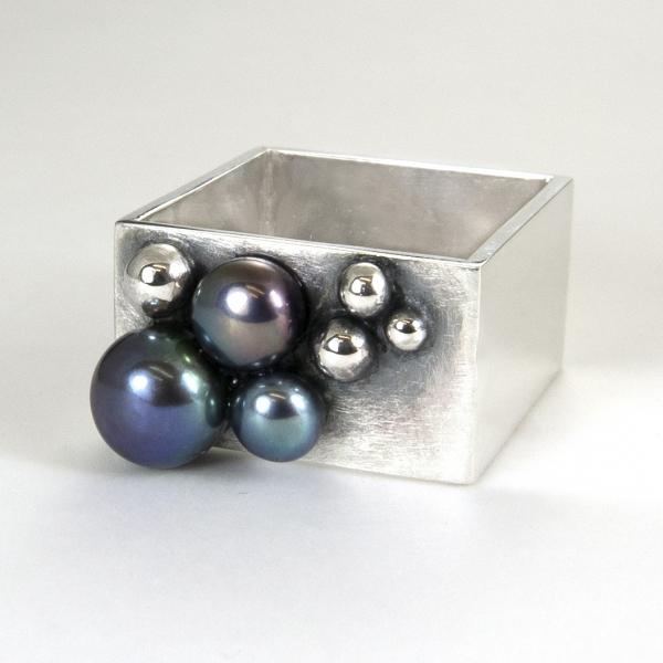 Szeroki kwadratowy pierścionek z perłami.