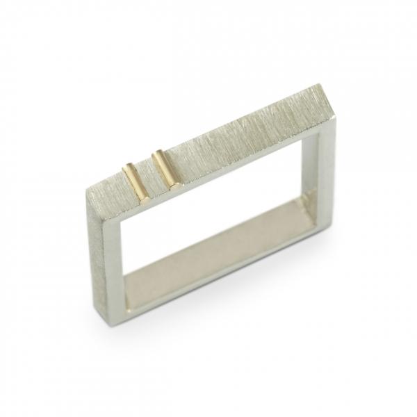 Pierścionek-kwadrat naznaczony złotem.